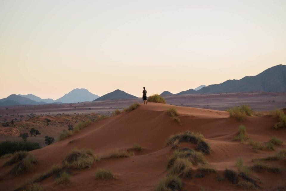 Standing on a dune looking out at the desert